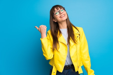 Young woman with yellow jacket on blue background pointing to the side to present a product