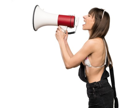 Young woman in bikini shouting through a megaphone over isolated white background