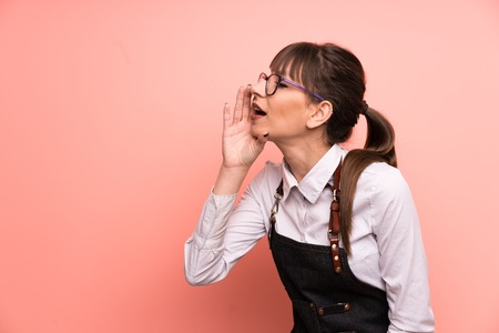 Young waitress over pink background shouting with mouth wide open