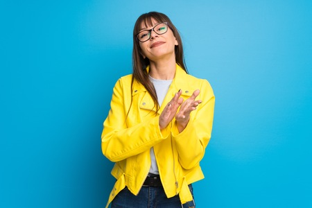 Young woman with yellow jacket on blue background applauding after presentation in a conference