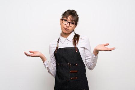 Young woman with apron having doubts while raising hands