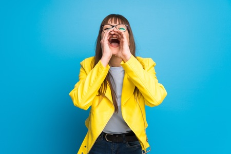 Young woman with yellow jacket on blue background shouting and announcing something Imagens