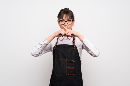 Young woman with apron showing a sign of silence gesture Imagens