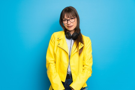 Young woman with yellow jacket on blue background with headphones