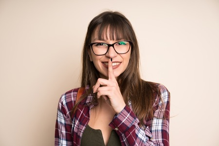 Young woman on ocher background doing silence gesture