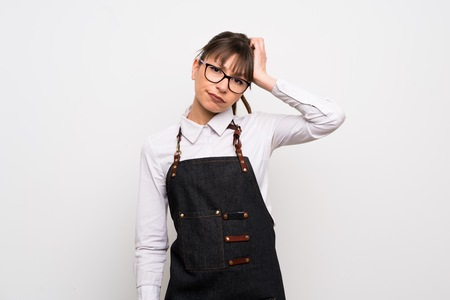 Young woman with apron with an expression of frustration and not understanding 版權商用圖片