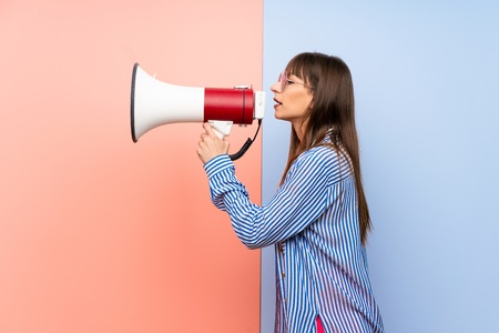 Young woman in bikini shouting through a megaphone