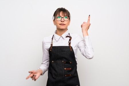 Young woman with apron making the gesture of madness putting finger on the head Standard-Bild