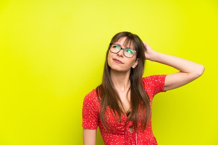 Young woman over green wall having doubts and with confuse face expression Banco de Imagens