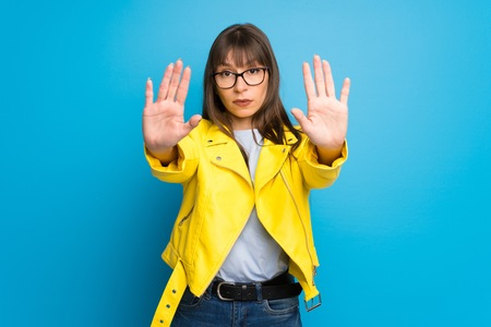 Young woman with yellow jacket on blue background making stop gesture for disappointed with an opinion