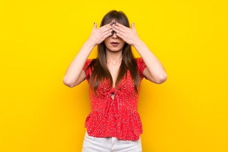 Young woman over yellow wall covering eyes by hands Stock Photo