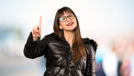 Woman with glasses showing and lifting a finger in sign of the best at outdoors