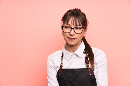 Young waitress over pink background standing and looking to the side