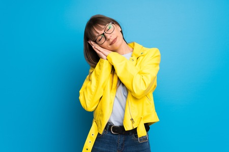 Young woman with yellow jacket on blue background making sleep gesture in dorable expression Imagens