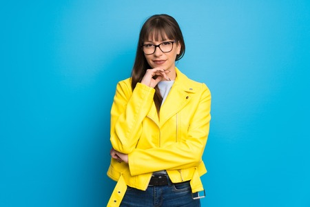 Young woman with yellow jacket on blue background smiling and looking to the front with confident face