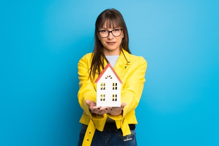 Young woman with yellow jacket on blue background holding a little house 版權商用圖片