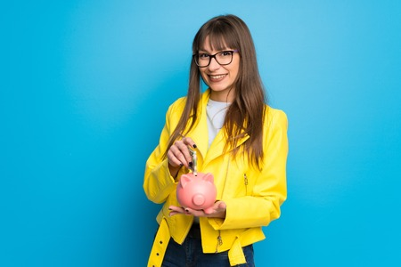 Young woman with yellow jacket on blue background taking a piggy bank and happy because it is full