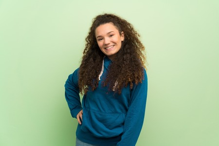 Teenager girl over green wall posing with arms at hip and smiling