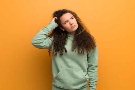 Teenager girl over ocher wall having doubts while scratching head