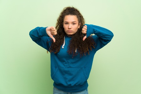 Teenager girl over green wall showing thumb down with both hands Imagens