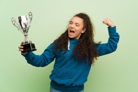 Teenager girl over green wall holding a trophy