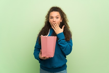 Teenager girl over green wall surprised and eating popcorns