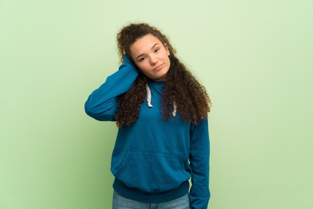 Teenager girl over green wall with an expression of frustration and not understanding