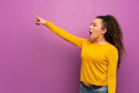 Teenager girl over purple wall pointing away
