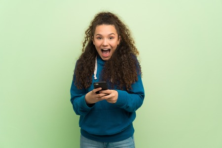 Teenager girl over green wall surprised with a mobile