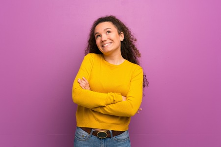 Teenager girl over purple wall looking up while smiling