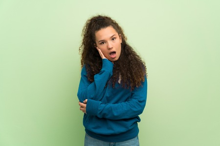 Teenager girl over green wall surprised and shocked while looking right