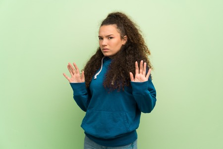Teenager girl over green wall making stop gesture with both hands