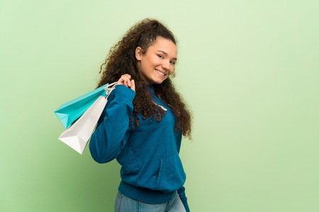 Teenager girl over green wall holding a lot of shopping bags