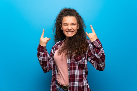 Teenager girl over blue wall making rock gesture