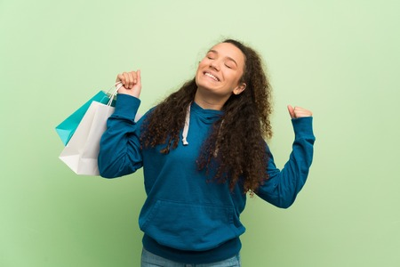 Teenager girl over green wall holding a lot of shopping bags in victory position Zdjęcie Seryjne