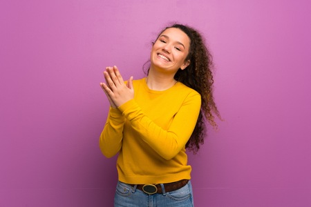 Teenager girl over purple wall applauding after presentation in a conference