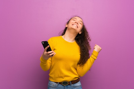 Teenager girl over purple wall with phone in victory position