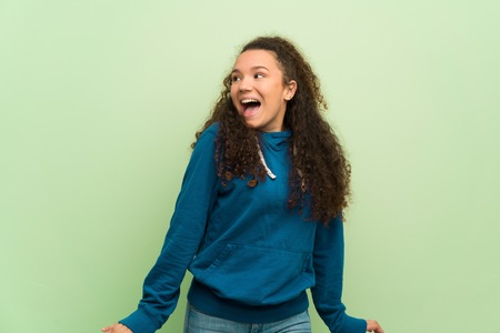 Teenager girl over green wall smiling