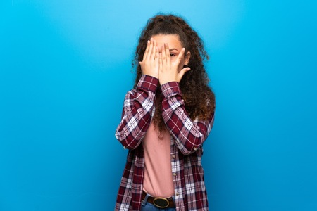 Teenager girl over blue wall covering eyes by hands and looking through the fingers Zdjęcie Seryjne