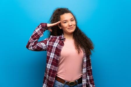 Teenager girl over blue wall saluting with hand