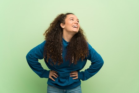 Teenager girl over green wall happy and smiling