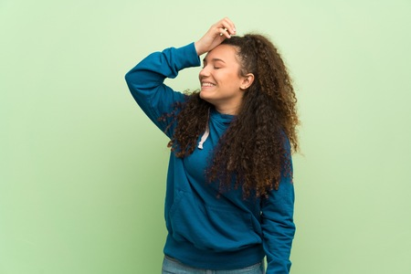 Teenager girl over green wall has just realized something and has intending the solution Zdjęcie Seryjne