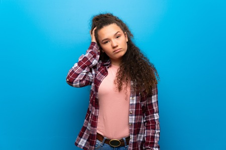 Teenager girl over blue wall with an expression of frustration and not understanding