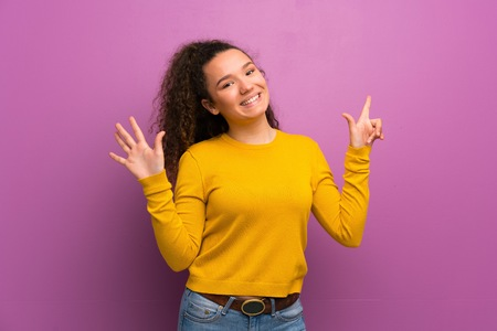 Teenager girl over purple wall counting seven with fingers Zdjęcie Seryjne