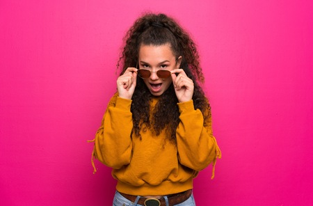Teenager girl over pink wall with glasses and surprised