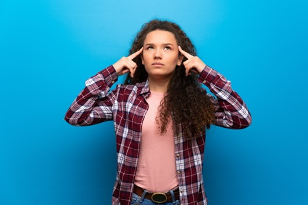 Teenager girl over blue wall having doubts and thinking
