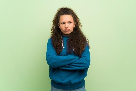 Teenager girl over green wall angry