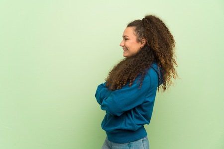 Teenager girl over green wall in lateral position