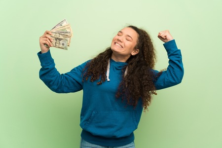 Teenager girl over green wall taking a lot of money Stock Photo