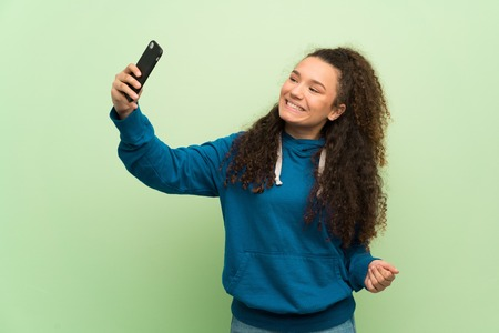 Teenager girl over green wall making a selfie